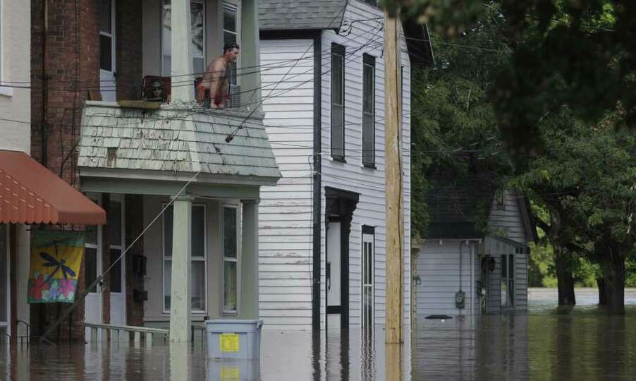A man looks over a balcony on the swollen Mohawk River on North St. in the Stockade section of Schen