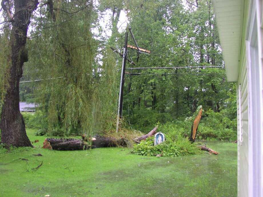 Storm damage from Hurricane Irene topples tree and telephone pole, but Blessed Mother remains unharmed. Photo: .