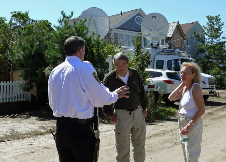 Police Chief Gary MacNamara, left, talks to some residents of Fairfield Beach Road Monday morning. Town officials were assessing the damage to determine whether residents who evacuated could return. Photo: Genevieve Reilly / Fairfield Citizen