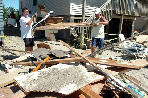 John Loeser and Brian McMahon move debris left behind from Sunday's storm as they clean up around their homes in the Lordship section of Stratford, Conn. Aug. 29th, 2011. Photo: Ned Gerard