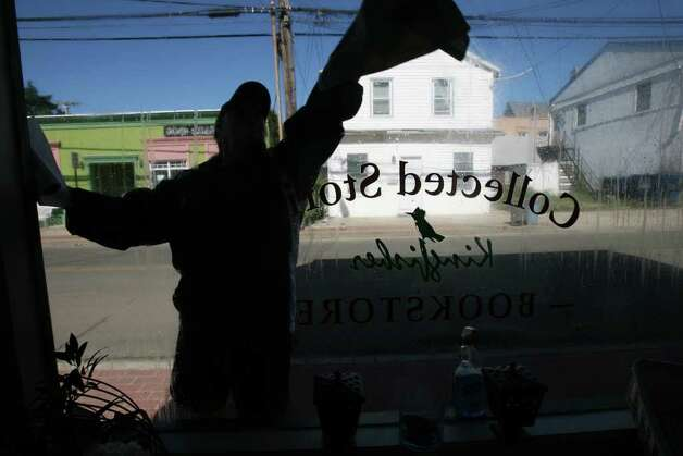 "Tyyne Catapano cleans the window of her bookstore, ""Wild Expressions"",  in the Walnut Beach area in Milford on Monday, August 28, 2011. The hurricane flooded the shop floor. Photo: B.K. Angeletti / Connecticut Post"
