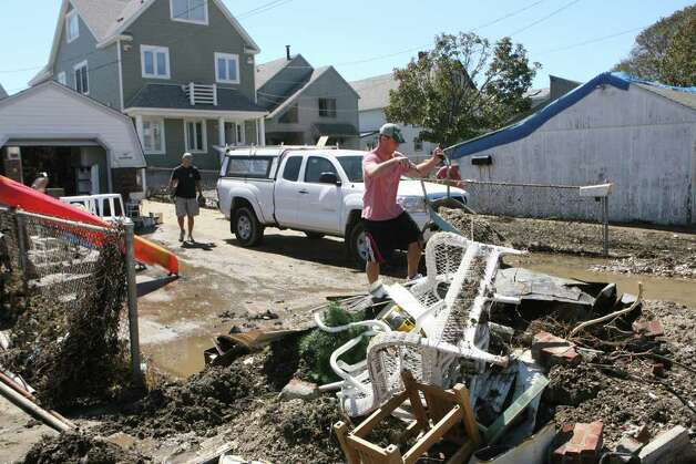 Craig Southard, of Fairfield,  helps clean up his parents home on Melba St. in Milford after hurricane Irene on Monday August 28, 2011. Photo: B.K. Angeletti / Connecticut Post
