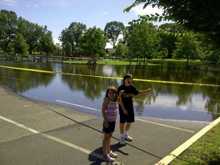 Delia Weinstein, 7, and Samuel Weinstein, 9, point to water overflowing in the Crossings parking lot in Colonie. In the backgound is the playground area. Photo: Paul Weinstein