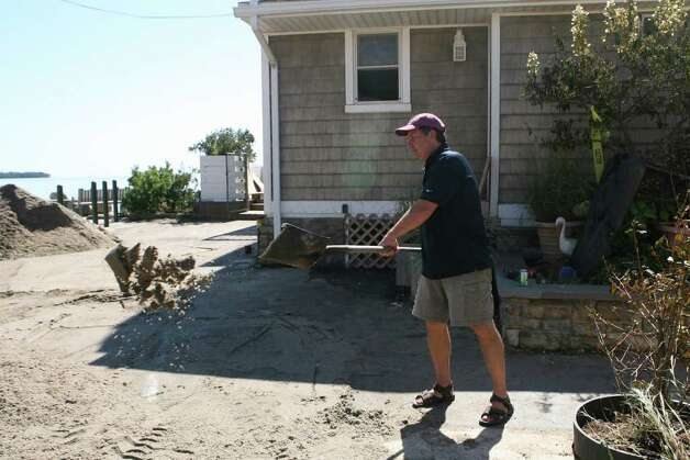Walt Oko shovels sand away from his home in the Walnut Beach area in Milford on Monday, August 28, 2011. Photo: B.K. Angeletti / Connecticut Post