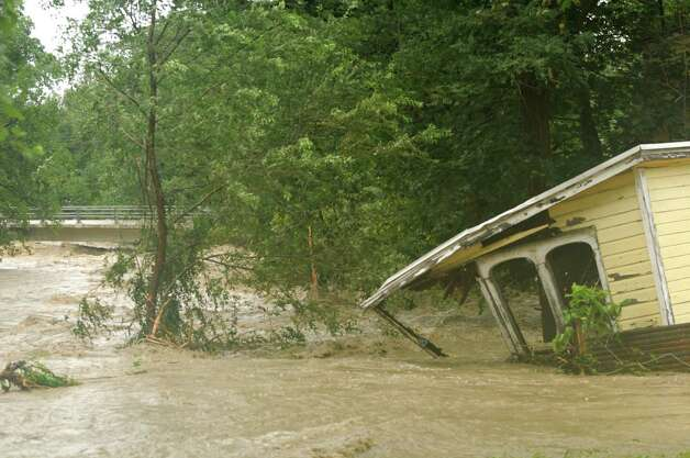 A Willowbrook Avenue structure in Selkirk is swept up by the nearby creek, Sunday afternoon Aug. 28, 2011. Tropical Storm Irene entered the Capital Region Sunday morning downing trees throughout Delmar, many are without power. (Will Waldron / Times Union) Photo: Will Waldron
