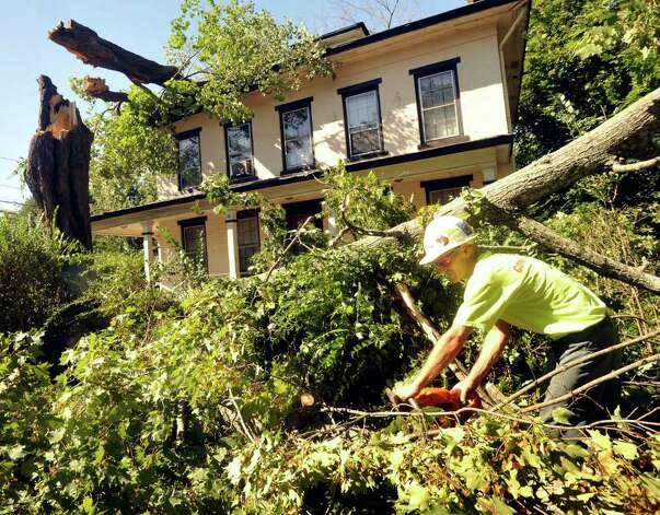 Doug Evanuska of the Danbury Forestry Department cuts a downed tree on Balmforth Avenue in Danbury, Monday, Aug. 29, 2011. The sugar maple on the house weighs about 4,000 pounds . Photo: Michael Duffy