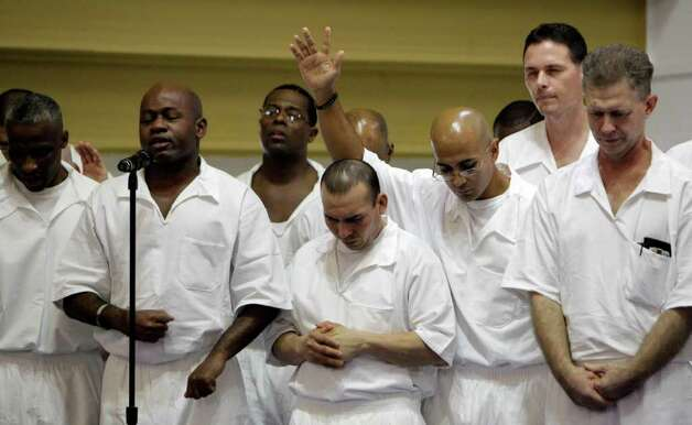 Prisoner members of the Darrington Chapel Gospel Choir perform at the Texas Department of Criminal Justice's Darrington Unit, 59 Darrington Unit Road, during a Convocation ceremony, in Rosharon. Texas prison officials, Houston lawmakers and representatives of Southwestern Baptist Theological Seminary celebrated the opening of the state's first 4-year prison seminary program.   The nondenominational program, sponsored by the TDCJ, Southwestern Baptist Theological Seminary, Southern Baptists of Texas Convention and the Heart of Texas Foundation, will train inmates who are serving lengthy sentences to become ministers. Once they graduate from the program, the inmates will go to other Texas prison facilities where they will minister to their fellow offenders. Photo: Melissa Phillip / © 2011 Houston Chronicle