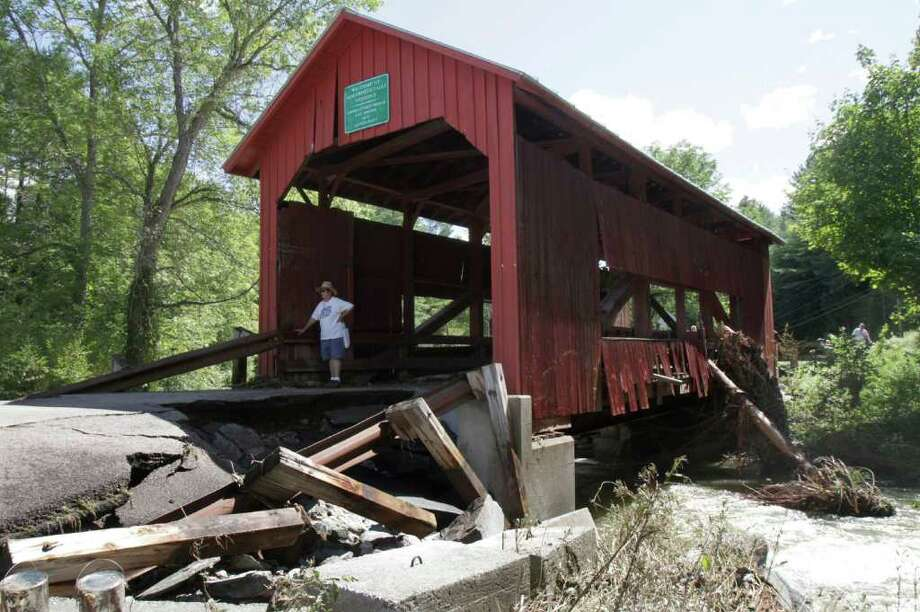 A damaged historic covered bridge spans Cox Brook in Northfield, Vt., Monday, Aug. 29, 2011, the day after Tropical Storm Irene dumped heavy rainfall across the region, causing flash floods. (AP Photo/Toby Talbot) Photo: Toby Talbot, STF / AP