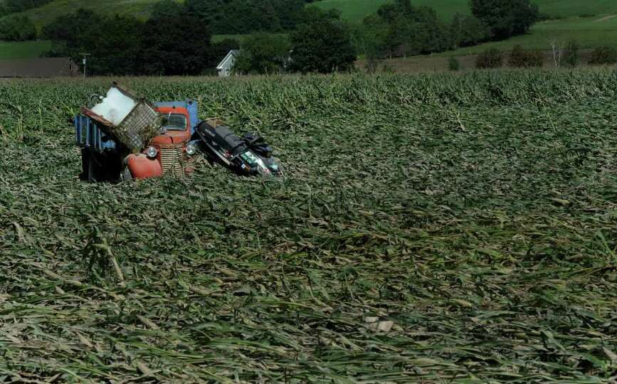 A farm vehicle collected a snow mobile and a harvest container as it sits in a corn field leveled by
