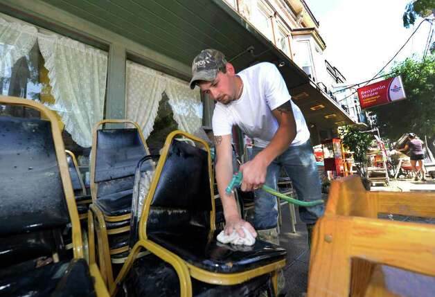 Jonathan Mickels cleans the mud and silt from the chairs at his mother-in-laws business Mrs. K's Restaurant in Middleburg, N.Y. Aug. 29, 2011.   (Skip Dickstein / Times Union) Photo: SKIP DICKSTEIN / 2011