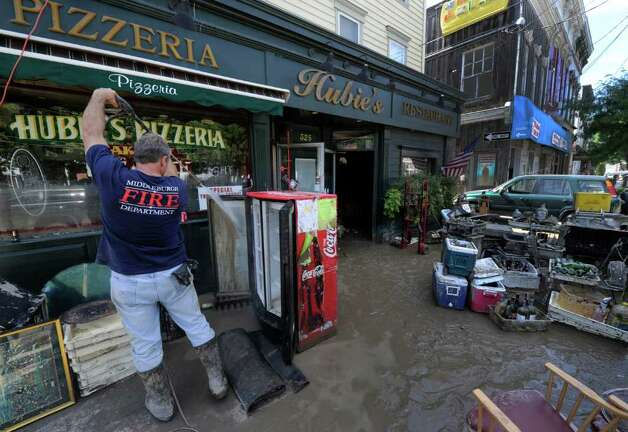 Kitch Paser uses a power washer to clean silt and mud from a cooler at  Hubie's Pizzeria in Middleburg, N.Y. Aug. 29, 2011.   (Skip Dickstein / Times Union) Photo: SKIP DICKSTEIN / 2011