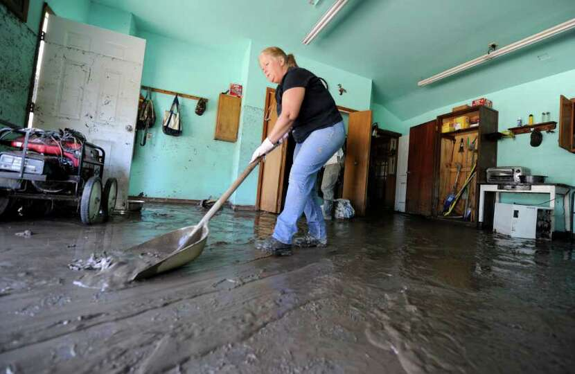 Carol Traver removes mud from the floor of her friends home after  the flood at the Lawyer residence