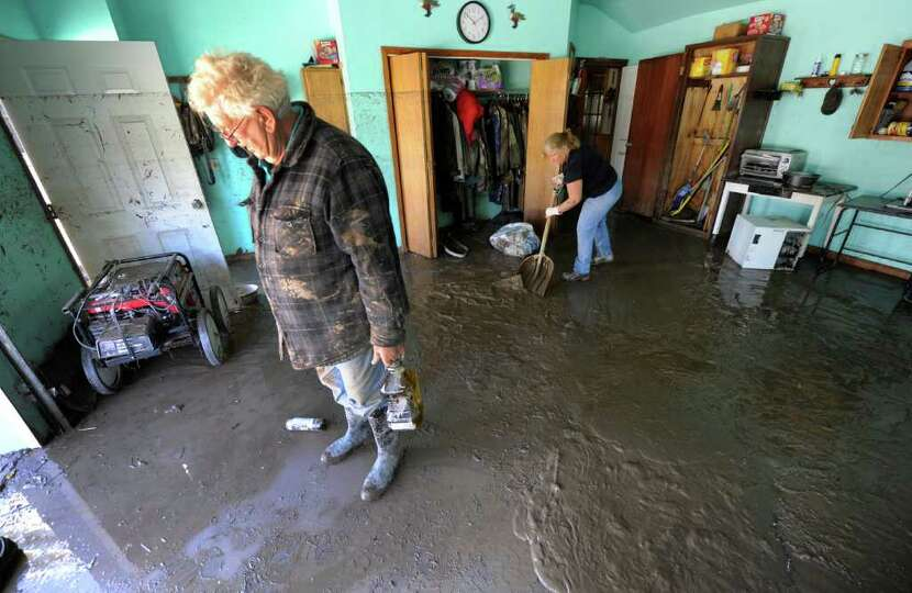 Otis Lawyer, left removes items from his garage where mud remains from the flood at his home on Main