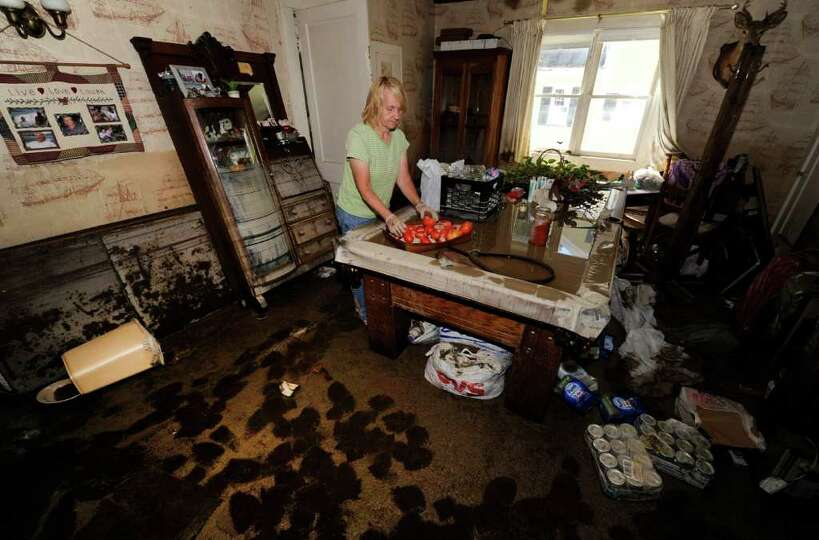 Joan Nelson removes items from a pool table where water remains from the flood at her home at 240 Ma