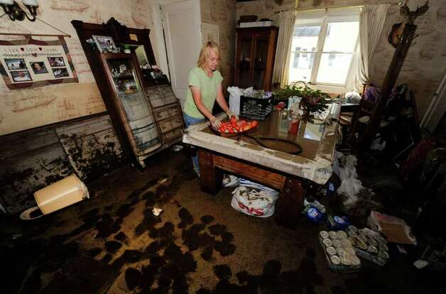 Joan Nelson removes items from a pool table where water remains from the flood at her home at 240 Main Street in Schoharie, N.Y. Aug. 29, 2011.   (Skip Dickstein / Times Union) Photo: SKIP DICKSTEIN / 2011