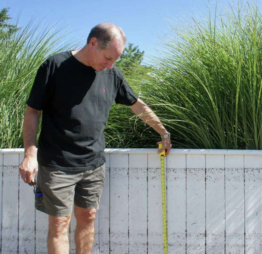 Saugatuck Shores resident Mark Altschuler measures the high water mark on a fence at his Pebble Beach Lane home on Monday, Aug. 29, 2011. Photo: Paul Schott / Westport News
