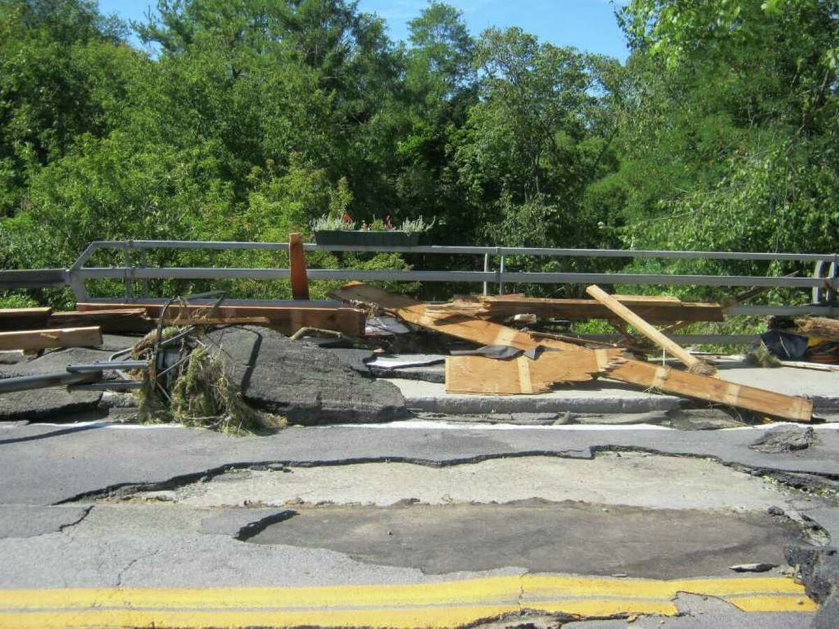 A bridge by the Fox Creek in Berne is covered with debris and shattered pavement, Monday Aug. 29, 2011. A nearby two-car garage was washed away.