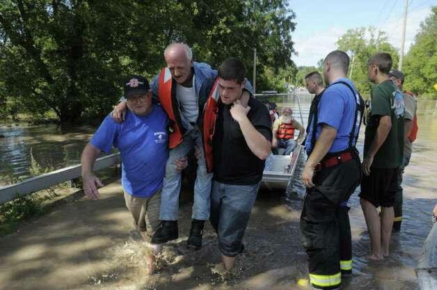 Doug Watson is carried off a boat by Andy Yuhasz, left, with the Schonowe Fire Company and Daniel Biddle, a resident who stayed to help others evacuate in Rotterdam Junction on Monday, Aug. 29, 2011.  Rotterdam Junction residents were evacuated by boat carrying them across a flooded section of Route 5s. (Paul Buckowski / Times Union) Photo: Paul Buckowski  / 00014438B