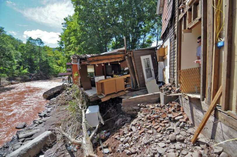 Eric Lenseth looks over the damage caused to his home by Hurricane Irene, on Monday Aug. 29, 2011,