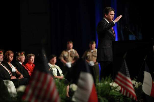 Governor Rick Perry salutes the audience as he speaks at the Veterans of Foreign Wars National Convention at the Henry B. Gonzalez Convention Center in San Antonio on Monday, August 29, 2011. Photo: LISA KRANTZ, LISA KRANTZ/lkrantz@express-news.net / lkrantz@express-news