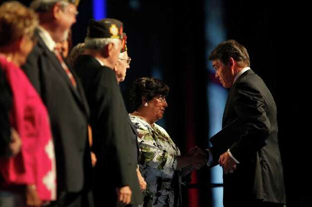 Governor Rick Perry greets participants on the stage after speaking at the Veterans of Foreign Wars National Convention at the Henry B. Gonzalez Convention Center in San Antonio on Monday, August 29, 2011. Photo: LISA KRANTZ, LISA KRANTZ/lkrantz@express-news.net / lkrantz@express-news