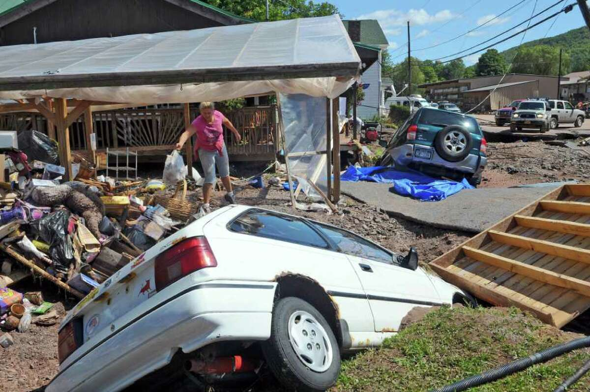 Natasha Shuster, co owner of the Catskill Mountain Country Store, cleans up from the damage caused by Hurricane Irene, on Monday Aug. 29, 2011, in Windham, NY. Two cars ended up in the shattered parking area in front of the store. (Philip Kamrass / Times Union)
