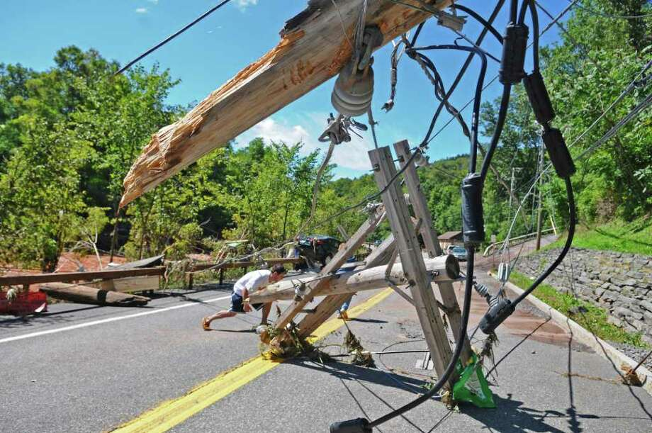 Pedestrians walk underneath a damaged, inactive power line on Main Street, caused by Hurricane Irene continues, on Monday Aug. 29, 2011,  in Windham, NY. (Philip Kamrass / Times Union) Photo: Philip Kamrass