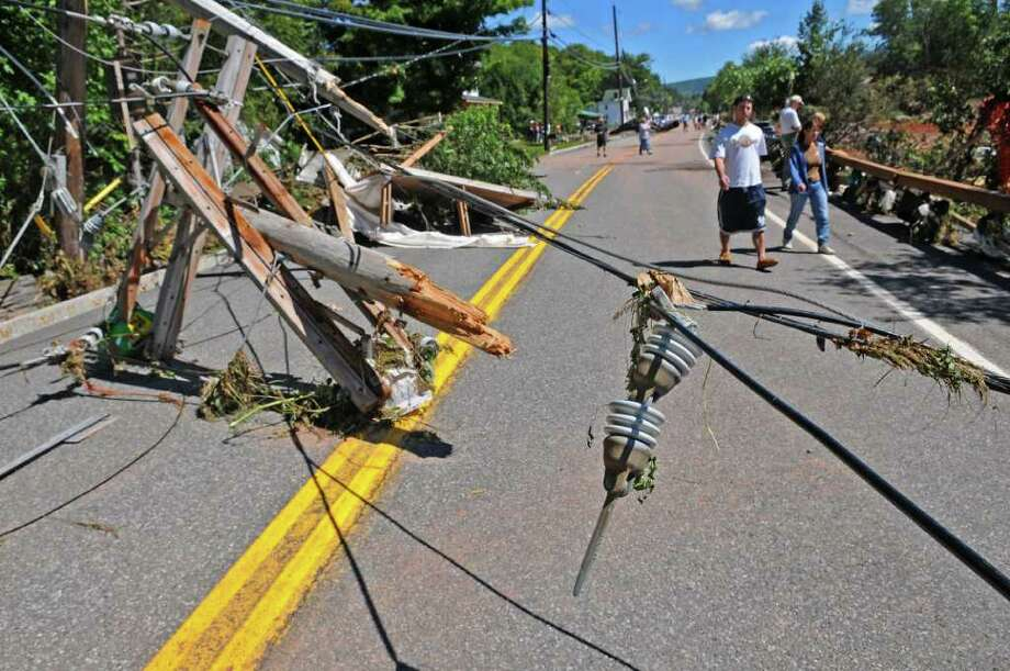 Pedestrians walk near a damaged, inactive power line on Main Street, caused by Hurricane Irene continues, on Monday Aug. 29, 2011,  in Windham, NY. (Philip Kamrass / Times Union) Photo: Philip Kamrass