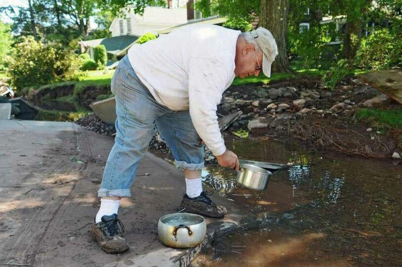 Peter Lucatuorto gathers water to use in his toilet, from a large puddle where a sidewalk used to be