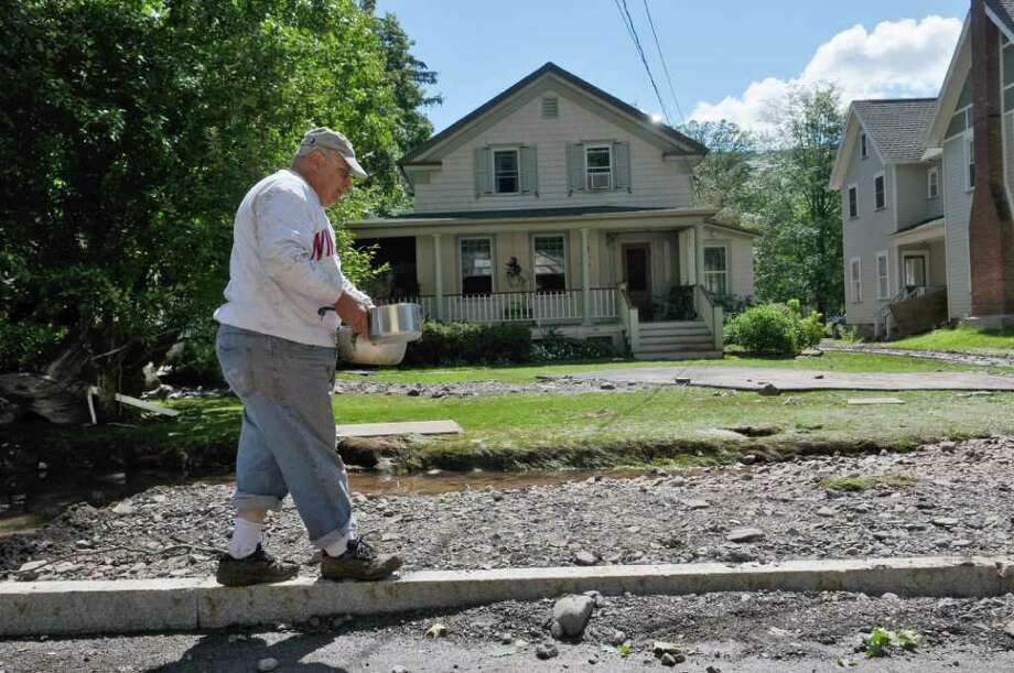 Peter Lucatuorto gathers water to use in his toilet, from a large puddle where a sidewalk used to be, in front of his house on Main Street, from damage caused by Hurricane Irene, on Monday Aug. 29, 2011,  in Windham, NY. (Philip Kamrass / Times Union) Photo: Philip Kamrass