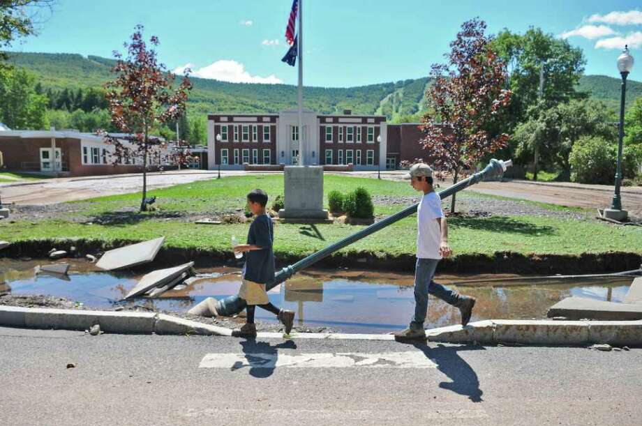 "Children walk in front of Windham Ashland Jewett Central School on Main Street, which sustained some damage on the first floor, caused by Hurricane Irene, on Monday Aug. 29, 2011,  in Windham, NY. District superintendent John Witkorko was optimistic that school would open soon. ""WAJ's roots are deep, and a little water will not uproot us,"" he said. He said that 410 students attend the K-12 school. (Philip Kamrass / Times Union) Photo: Philip Kamrass"