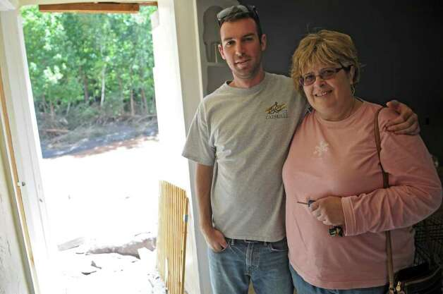 Eric Lenseth stands with his aunt Anne Brabazon near where their house broke away during Hurricane Irene, on Monday Aug. 29, 2011,  in Windham, NY. Eric got his aunt Anne Brabazon out of the house before this two story  section was swept away by the swollen Batavia Kill. (Philip Kamrass / Times Union) Photo: Philip Kamrass