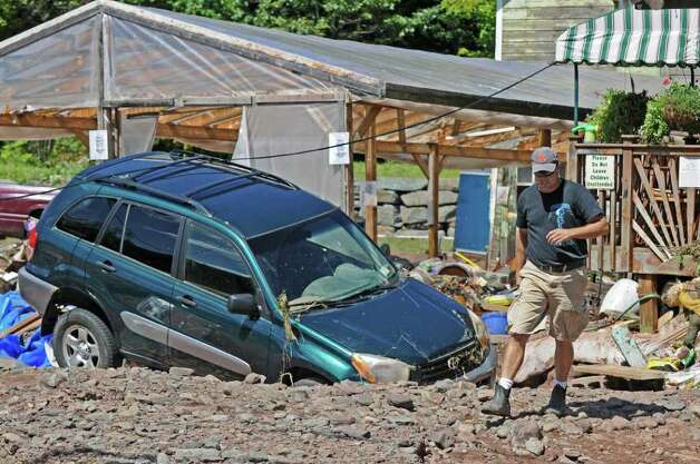 A damaged car ended up in the damaged parking lot of the Catskill Mountain Country Store during Hurricane Irene, on Monday Aug. 29, 2011,  in Windham, NY.   (Philip Kamrass / Times Union) Photo: Philip Kamrass