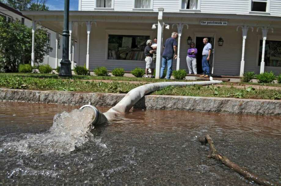 The Patchwork Company, a fabric store, sustained heavy flood damage during Hurricane Irene, seen here pumping water onto Main Street on Monday Aug. 29, 2011,  near Windham, NY.   (Philip Kamrass / Times Union) Photo: Philip Kamrass