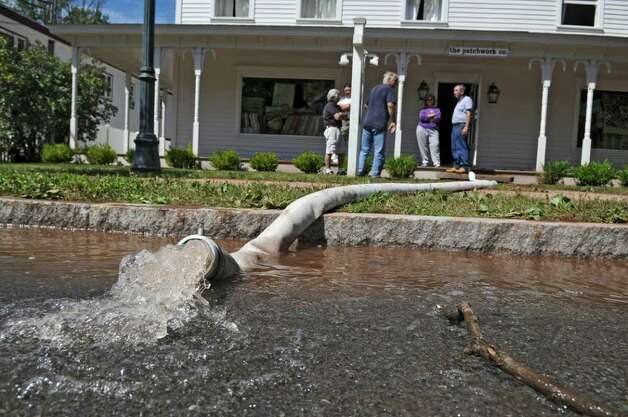 UPDATED CAPTION -The Patchwork Company, a fabric store, sustained heavy flood damage during Hurricane Irene, seen here pumping water onto Main Street on Monday Aug. 29, 2011,  in Windham, NY.   (Philip Kamrass / Times Union) Photo: Philip Kamrass