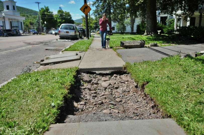 A pedestrian walks near a damaged sidewalk on Main Street while work continues on cleaning up the da
