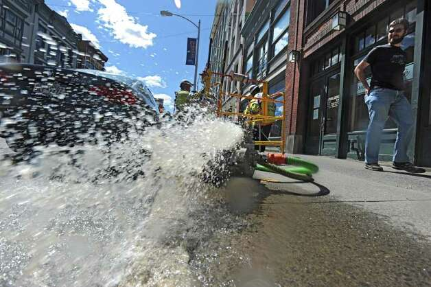 City workers try and pump the water out of underground crevices where electrical wires to local restaurants are in Troy, N.Y. on Monday, Aug. 29, 2011. Hurricane Irene caused major damage and flooding in the Capital District. (Lori Van Buren / Times Union) Photo: Lori Van Buren