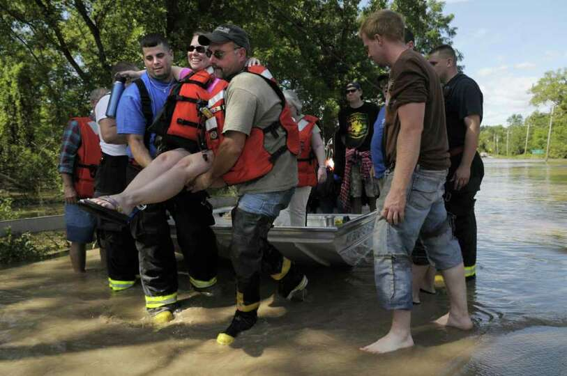 Resident Michelle Buonome is carried off a boat by firefighter Ben Kruger, left, with the Carman Fir