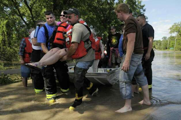 Resident Michelle Buonome is carried off a boat by firefighter Ben Kruger, left, with the Carman Fire Company and John Konik, chief of the Schonowe Fire Company in Rotterdam Junction on Monday, Aug. 29, 2011.  Rotterdam Junction residents were evacuated by boat carrying them across a flooded section of Route 5s. (Paul Buckowski / Times Union) Photo: Paul Buckowski  / 00014438B