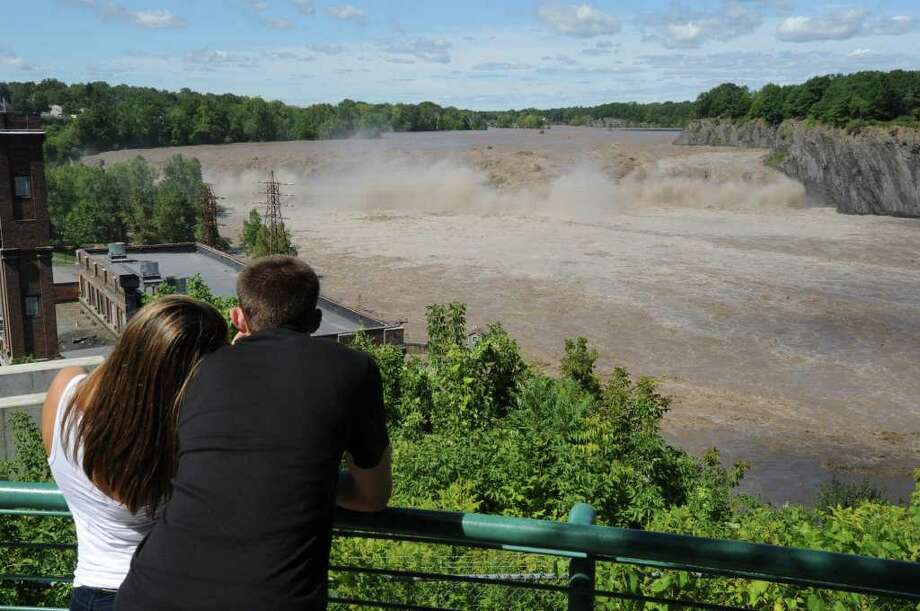 Maggie Maloney of Cohoes and Chris White of Green Island look at the intense water rushing over the Cohoes Falls in Cohoes, N.Y. on Monday, Aug. 29, 2011. Hurricane Irene caused major damage and flooding in the Capital District. (Lori Van Buren / Times Union) Photo: Lori Van Buren