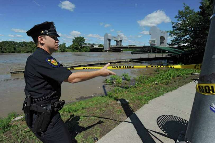 Officer Martin Furciniti puts up a police caution tape outside the Dinosaur Barbecue restaurant whic