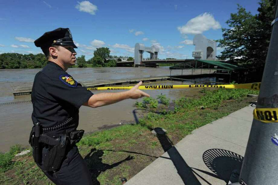Officer Martin Furciniti puts up a police caution tape outside the Dinosaur Barbecue restaurant which flooded from water that overflowed from the Hudson River in Troy, N.Y. on Monday, Aug. 29, 2011. Hurricane Irene caused major damage and flooding in the Capital District. (Lori Van Buren / Times Union) Photo: Lori Van Buren