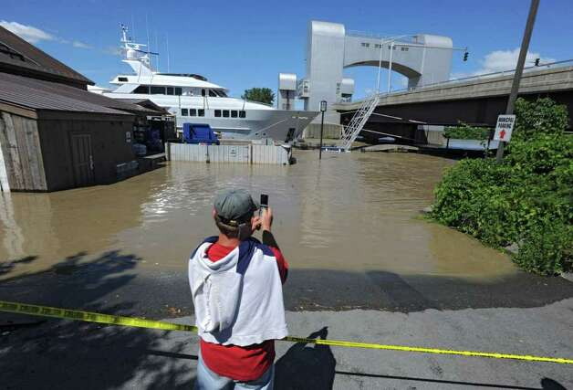 Leejay Defreest of Troy takes photos of a boat stuck behind the Dinosaur Barbecue restaurant which was flooded from water that overflowed from the Hudson River in Troy, N.Y. on Monday, Aug. 29, 2011. Hurricane Irene caused major damage and flooding in the Capital District. (Lori Van Buren / Times Union) Photo: Lori Van Buren