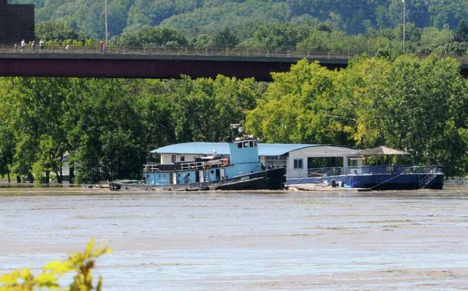 The Rusty Anchor floating bar and restaurant on the Watervliet side of the Hudson River is secured by a tugboat for fear of it breaking away into the Hudson River in Troy, N.Y. on Monday, Aug. 29, 2011. Hurricane Irene caused major damage and flooding in the Capital District. (Lori Van Buren / Times Union) Photo: Lori Van Buren
