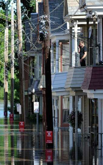 A man on Ingersall Avenue in Schenectady, N.Y. looks down from his second floor apartment as water r