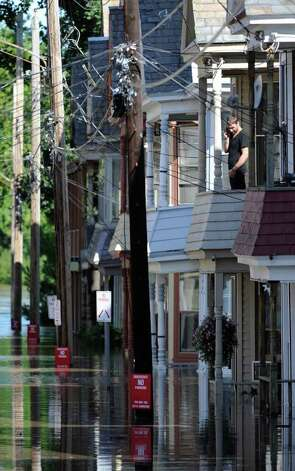 A man on Ingersall Avenue in Schenectady, N.Y. looks down from his second floor apartment as water rises from the Mohawk River and floods homes on the street Aug. 29, 2011.  . (Skip Dickstein / Times Union) Photo: SKIP DICKSTEIN / 2011