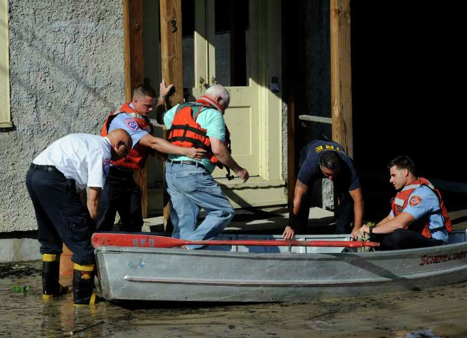 James Poier is assisted by Schenectady Fire Department personel to a boat that took him to his home at 5 Ingersall in Schenectady, N.Y. to retrieve medication as flood waters rises from the Mohawk River and floods homes on the street. (Skip Dickstein / Times Union) Photo: SKIP DICKSTEIN / 2011
