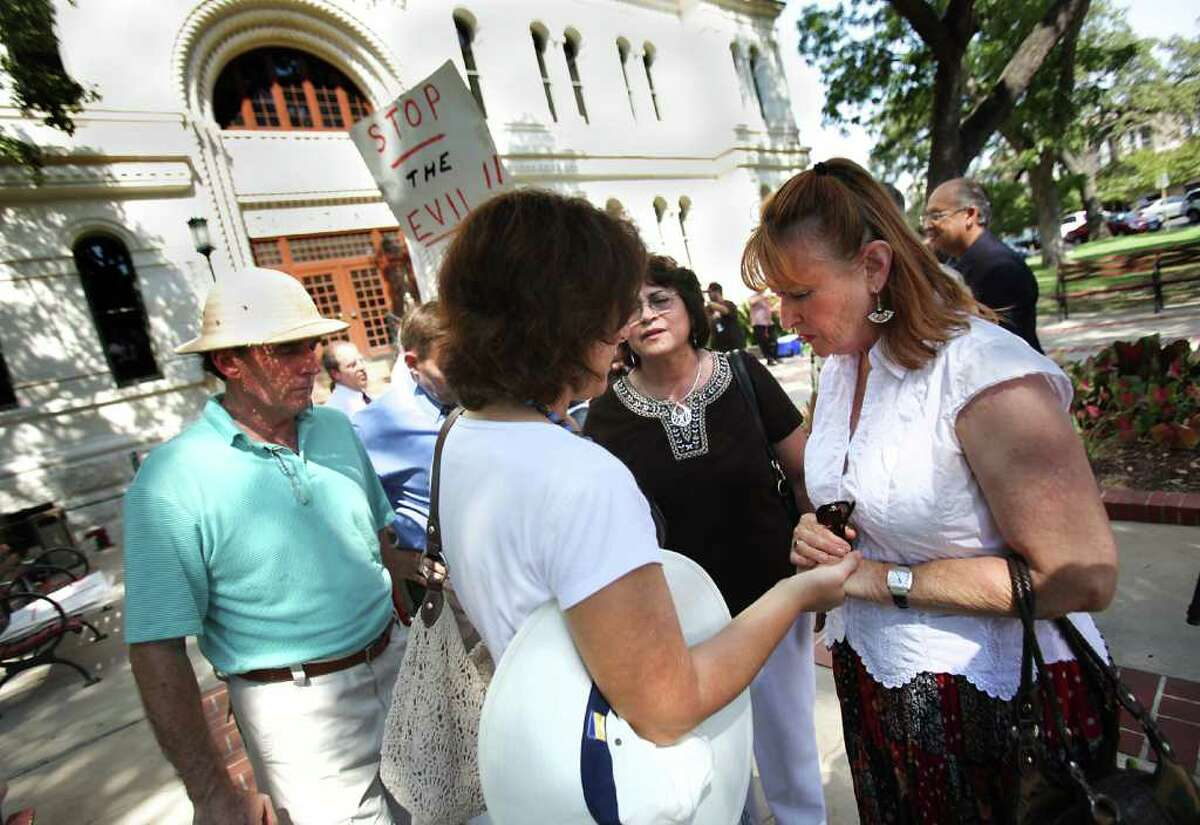 Marilyn Wheeler, right to left, Pastor Berta Brannstrom, Maryon Baumgartner, and Pastor Richard Wheeler, pray for a young woman who had a confrontation with the group of local Christian conservative pastors that held a press conference on the steps of City Hall to voice their objections to the city's proposal to offer domestic partner benefits to city employees.
