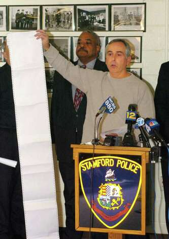 File photo 2005: Stamford Police Department announces the arrest of Harry Gonzalez and Jennifer Kos, two suspects in the murder of Joanne Trautwein. Captain Richard Conklin holds up the 'rap' sheet of Harry Gonzalez. Photo: Paul Desmarais, ST / Stamford Advocate