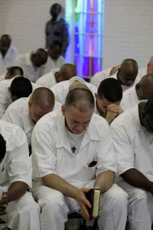 Prisoners at the Texas Department of Criminal Justice's Darrington Unit, 59 Darrington Unit Road, pray during a Convocation ceremony    Monday, Aug. 29, 2011, in Rosharon. Texas prison officials, Houston lawmakers and representatives of Southwestern Baptist Theological Seminary celebrated the opening of the state's first 4-year prison seminary program.   The nondenominational program, sponsored by the TDCJ, Southwestern Baptist Theological Seminary, Southern Baptists of Texas Convention and the Heart of Texas Foundation, will train inmates who are serving lengthy sentences to become ministers. Once they graduate from the program, the inmates will go to other Texas prison facilities where they will minister to their fellow offenders. Photo: Melissa Phillip, Houston Chronicle / © 2011 Houston Chronicle